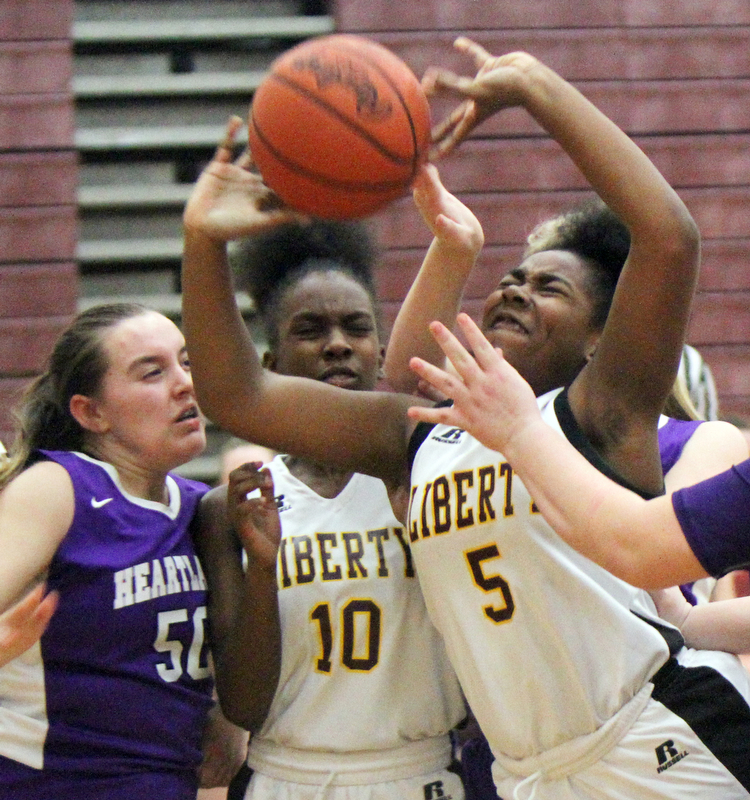 William D Lewis The Vindicator  Liberty's Delia Watson(5) shoots around Heartland's Megan Johnson (50) during 2-21-18 action at Liberty. Liberty's Sierra Williams(10) is at center.