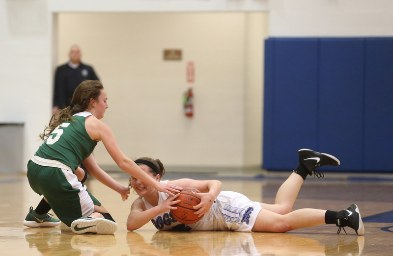 Poland guard Kat Partika (22) and Ursuline's Cara McNally (5) fight over a loose ball after Partika dove for itin the fourth quarter of an Division II sectional final high school basketball game, Thursday, Feb. 22, 2018, in Poland. Poland won 50-49...(Nikos Frazier | The Vindicator)