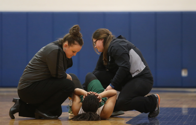 Ursuline's Dayshonette Harris (1) is examined by a trainer after an injury in the fourth quarter of an Division II sectional final high school basketball game, Thursday, Feb. 22, 2018, in Poland. Poland won 50-49...(Nikos Frazier | The Vindicator)