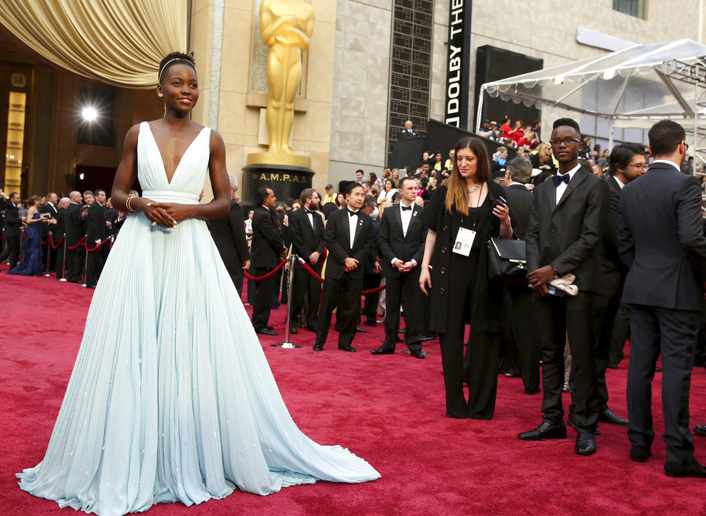 """FILE - In this March 2, 2014 file photo, Lupita Nyong'o arrives at the Oscars in Los Angeles. Nyong'o, wearing a light blue Prada gown, won the Oscar for best supporting actress for her role in """"12 Years a Slave."""" (Photo by Matt Sayles/Invision/AP, File)"""