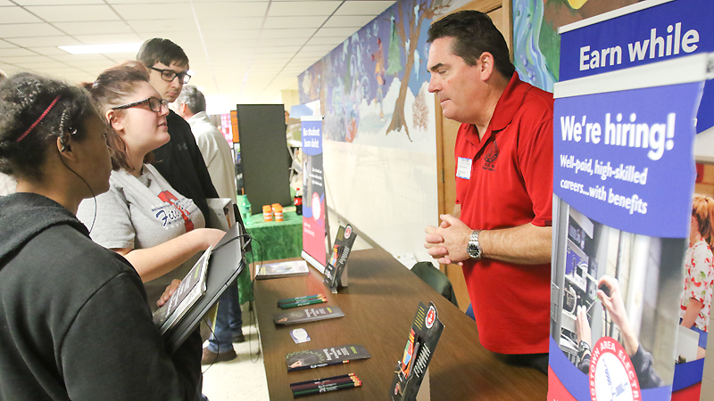 ROBERT K. YOSAY | THE VINDICATOR From left, seniors Gianna Prunell and Sarah Mazon and junior Alex Burns talk to Ed Emerick from the Youngstown Area Electrical Joint Apprenticeship Training Committee during a trade fair Thursday at Austintown Fitch High School.