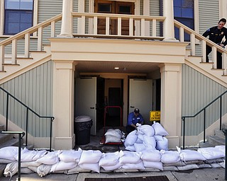 Provincetown DPW worker Paulo Andrade moves sand bags around the lower entrance to town hall as preparations are underway for the approaching storm, Thursday, March 1, 2018 in Provincetown, Mass. (Steve Heaslip/The Cape Cod Times via AP)