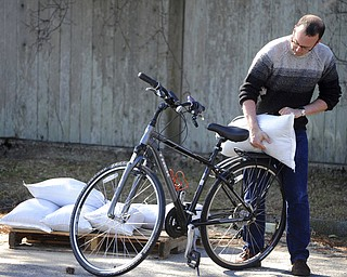 Brian Croteau loads sandbags onto his bike for a short ride back to his Commercial Street home to help secure it as preparations are underway for the approaching storm, Thursday, March 1, 2018 in Provincetown, Mass. Airlines, officials and residents braced Thursday for potentially widespread coastal flooding from a major Nor'easter bearing down on a large swath of the East coast. (Steve Heaslip/The Cape Cod Times via AP)