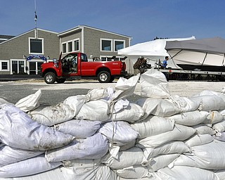 Sandbags fill  the boat ramp at Outermost Harbor Marine as crews move the last of several boats to a safer spot as preparations are underway for the approaching storm, Thursday, March 1, 2018 in Chatham, Mass. (Steve Heaslip/The Cape Cod Times via AP)