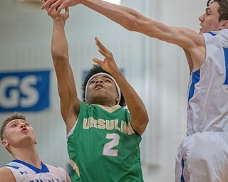 Ursuline's Daysean Harris shoots the ball between Poland defenders Brandon Barringer and Dan Kramer during Poland's 68-47 sectional tournament win in Poland on Friday night...Photo by Dianna Oatridge.