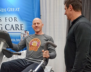 Jason Pridon from Muscle Connection talks with Paul Minotti who is trying out a Cardio Strider at the Valley Health and Wellness Expo at the Covelli Centre on Saturday, March 3, 2018...Photo by Scott Williams, The Vindicator.