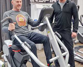 Jason Pridon, right, from Muscle Connection talks with Paul Minotti who is trying out a Cardio Strider at the Valley Health and Wellness Expo at the Covelli Centre on Saturday, March 3, 2018...Photo by Scott Williams, The Vindicator.