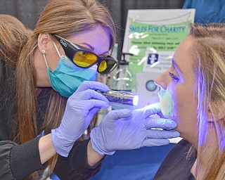 Sheila Johnston gives Nicole Bodnar a free oral cancer screening at the Valley Health and Wellness Expo held a Covelli Centre on Saturday March 3, 2018.  Braydich Dental, who was offering the free screening, also gave away more than 700 toothbrushes at the event...Photo by Scott Williams, The Vindicator.
