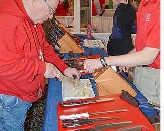 Dennis Tucholski tries out a knive from The Cutco Kitchen as Nate Bratton explains their product at the HBA Home and Garden Show held at Mr. Anthony's in Boardman on Saturday, March 3, 2018...Photo by Scott Williams, The Vindicator.