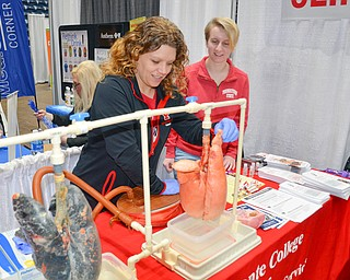 Tammy Kemble, left, pumps air into two lungs, one representing a smoker's lungs and the other representing clean lungs, as Kristina Ritch observes. Both ladies are respiratory care majors at Youngstown State University and were volunteering at the Bitonte College of Health and Human Services table at the Valley Health and Wellness Expo, held at Covelli Center on Saturday, March 3, 2018...Photo by Scott Williams, The Vindicator.