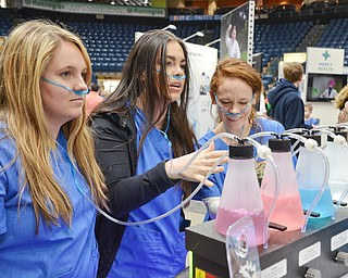 Three Mercy College of Ohio students, from left to right, Autumn Miller, Lauren McIntosh, and Maria Patsko try out an Euphorium Oxygen Bar at the Boardman Medical Supply booth at the Valley Health and Wellness Expo at the Covelli Centre on Saturday March 3, 2018.  An Euphorium Oxygen Bar is recreational oxygen and can be rented for private events and parties. ..Photo by Scott Williams, The Vindicator..