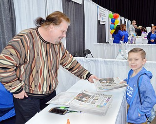 John Borzea hands 7 year old Tommy Zimmerlee a copy of SaturdayÕs edition of The Vindicator at the Valley Health and Wellness Expo held at Covelli Centre on Saturday March 3, 2018.  The Vindicator was a sponsor of the event...photo by Scott Williams, The Vindicator..