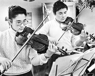 The last rehearsal: Brother and sister duet Maria (12th grade) and Paul (11th grade) Watanakunakorn of Boardman High School practice on their violins Saturday at Canfield High School prior to playing in a music competition sponsored by District V of the Ohio Music Educators Association.  More than 1,200 high school students participated in competitions at both Canfield and Frank Ohl Middle School, Austintown. ..This photo first ran in The Vindicator on Sunday, February 8, 1987...Photo by William D. Lewis, The Vindicator.