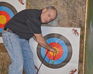 Dan Donoghue, with the Ohio Department on Natural Resources, pulls arrows out of a target at The Sportsman's Hunting and Fishing Supershow and Sale at the Metroplex Expo Center in Girard, Ohio on Sunday March 4, 2018. ODNR had a trailer set up inside the Expo Center and were teaching guests how to properly use a bow...Photo by Scott Williams - The Vindicator.