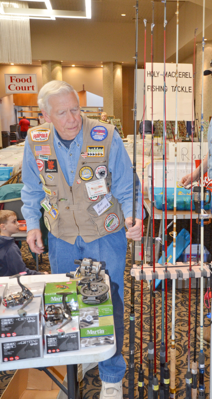 Mike Wohlever, from Amherst, Ohio, tends to his fishing poles set up at his booth at The Sportsman's Hunting and Fishing Supershow and Sale at the Metroplex Expo Center in Girard, Ohio on Sunday, March 4, 2018.  Wohlever hosts the Holy Mackerel flea market in Oberlin, Ohio in April...Photo by Scott Williams - The Vindicator.