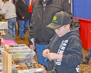 Adam Yarian, age 9, tinkers with some outdoor hunting gear as his grandfather Carl Buhn, both of New Waterford, Ohio, watches at The Sportsman's Hunting and Fishing Supershow and Sale at the Metroplex Expo Center in Girard, Ohio on Sunday March 4, 2018. ..Photo by Scott Williams - The Vindicator.