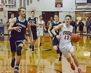 Connor Tamarkin (#13) of Howland moves the ball down court around Carson Ryan (#5) of Struthers during their Thursday, March 8, 2018 game at Boardman High School...Photo by Scott Williams - The Vindicator.