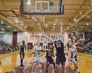 Struthers' Ryan Leonard (#20) and Adrian Brown (#10) try to put points on the board as Howland's Connor Tamarkin (#13) and Nathan Barrett (#40) try to block during their Thursday, March 8, 2018 game at Boardman High School...Photo by Scott Williams - The Vindicator.