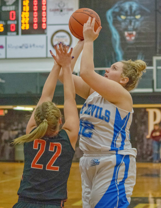 Leslie Burnip takes a jumper from the baseline with Kirsten Shoup of Dalton defending in a Division IV regional semifinal at Massillon Perry High School on Thursday.   Photo by Bob Ettinger.