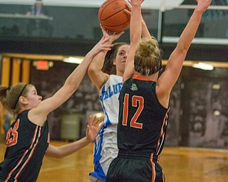 Izzy Perez of Lisbon pulls up for a jumper as Brennah Arnold (left) and Emma Cannon defend in a Division IV regional semifinal at Massillon Perry High School on Thursday.