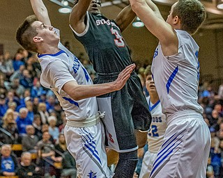 Struthers' Kevin Traylor drives to the basket between Lakeview defenders TJ Lynch (L) and Daniel Evans (R) during Lakeview's 72-59 win for the Division II District Championship in Boardman on Saturday...Photo by Dianna Oatridge.
