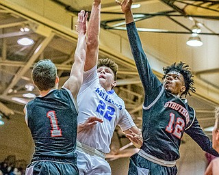 Lakeview's Drew Munno splits through Struthers' defenders Isiah Torrance (L) and Brandon Washington (R) on the way to the hoop Lakeview's 72-59 win at Boardman on Saturday in the Division II District Final...Photo by Dianna Oatridge.