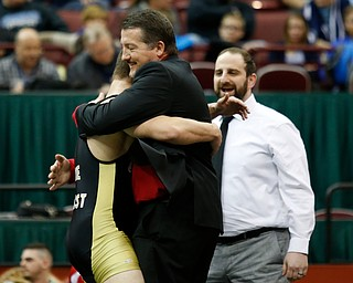 Canfield's David Crawford, left, gets a hug from his father David as his coach Steve Pitts looks on following Carwford 5-3  182 pound championship match win over St. Vincent-St. Mary's David Heath during the Division II Ohio state wrestling tournament at the Ohio State University Saturday, March 10, 2018. (Photo by Paul Vernon)
