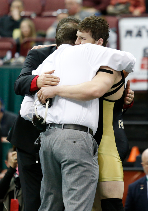 Canfield's Tyler Stein, right, hugs coaches Steve Pitts, center, and David Crawford following his 7-3  220 pound championship match win over Maumee's Brandon Phillips during the Division II Ohio state wrestling tournament at the Ohio State University Saturday, March 10, 2018. (Photo by Paul Vernon)