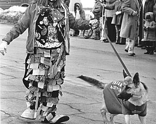 "A German Shepherd wearing the Irish green?  Thomas Davison, an Aut Mori Grotto clown, has them all fooled as he walks his ""Irish Setter.""..Photo taken March 11, 1984...Photo is by Robert K. Yosay."