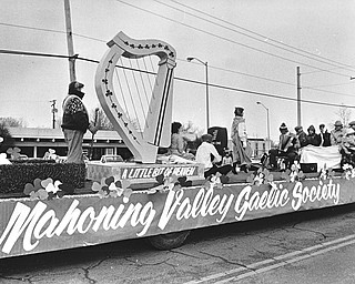 The luck of the Irish didn't keep the chilly temperatures away, so the riders on the Mahoning Valley Gaelic Society float use a blanket to keep warm while an Irish step dancer braves the biting winds to perform...Photo taken March 11, 1984...Photo by Robert K. Yosay - The Vindicator.