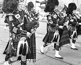 The MacCallum Highlanders Pipe and Drums of Akron march past green-tinted snowbanks on Route 224 during the sixth annual St. Patrick's Day Parade, held for the first time in Boardman...Photo taken on March 11, 1984...Photo by Robert K. Yosay - The Vindicator.