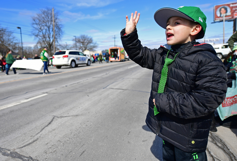 "BOARDMAN, OHIO - MARCH 11, 2018: Tyler Divto 6, of Streetsboro waives while saying ""Happy Saint Patricks Day"" to people marching on Market Street during the Mahoning Valley St. Patrick's Day Parade. DAVID DERMER 