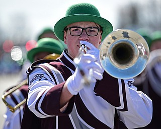 BOARDMAN, OHIO - MARCH 11, 2018: Boardman junior Matthew Welton plays his trombone while marching with the Boardman High School Marching Band on Market Street during the Mahoning Valley St. Patrick's Day Parade. DAVID DERMER | THE VINDICATOR