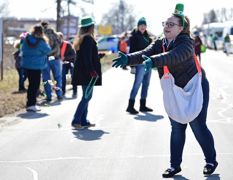BOARDMAN, OHIO - MARCH 11, 2018: Vindicator reporter Amanda Tonoli throws out some candy while marching on Market Street during the Mahoning Valley St. Patrick's Day Parade. DAVID DERMER | THE VINDICATOR