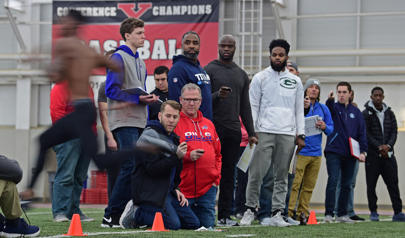 YOUNGSTOWN, OHIO - MARCH 13, 2018: Scouts from different NFL and CFL teams watch as Youngstown State's Alvin Bailey sprints through the finish line during the 40 yard dash during the Youngstown State football pro day, Tuesday morning at the Watts Indoor Facility. DAVID DERMER | THE VINDICATOR