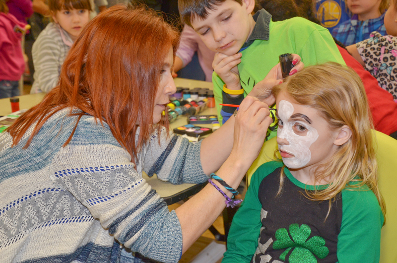 Maria Rosensteel, a 7th grade teacher at Campbell, paints a face on Abby Lencyk, 2nd grade student at South Range, as Oliver Ruediger, 2nd grade student at Campbell, waits his turn at Campbell Community Night at Campbell K-7 School on Thursday, March 15, 2018...Photo by Scott Williams - The Vindicator.
