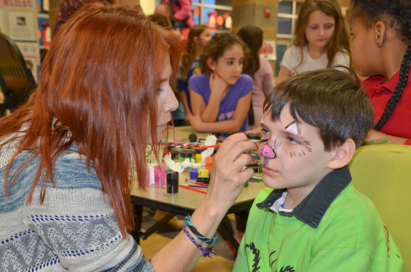 Oliver Ruediger, 2nd grade, gets his face painted by Maria Rosensteel, 7th grade teacher, at Campbell Community Night at Campbell K-7 School on Thursday, March 15, 2018...Photo by Scott Williams - The Vindicator.