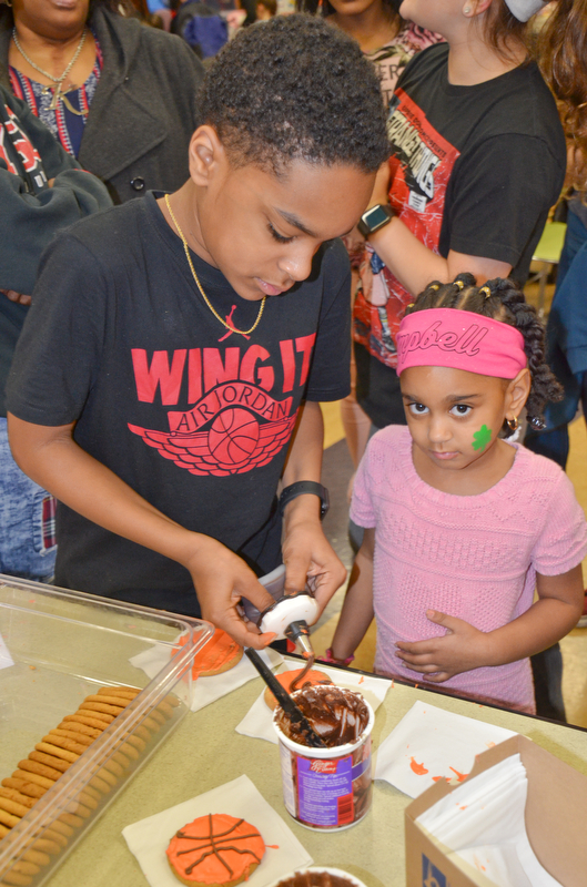 Jabari Rushton, left; 7th grade, helps his sister Serenity Cunningham, right; kindergarten, decorate some basketball cookies at Campbell Community Night at Campbell K-7 School on Thursday, March 15, 2018...Photo by Scott Williams - The Vindicator.