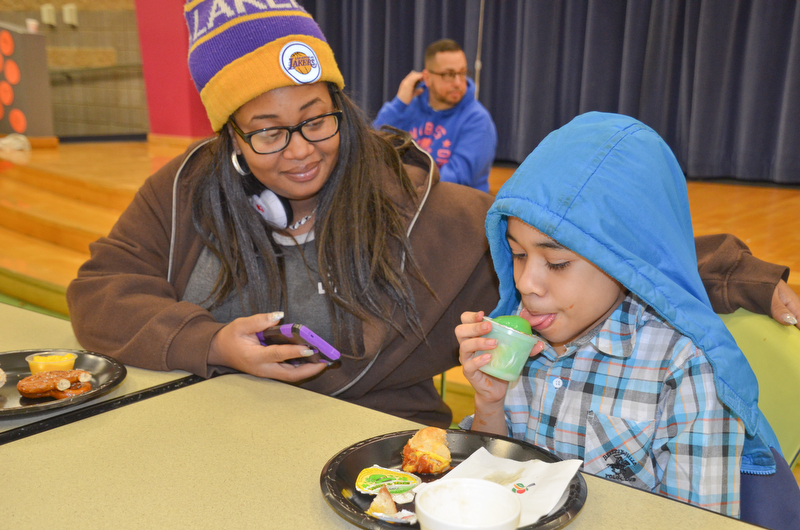 DaVon Curry, 5th grade, enjoys a frozen-ice treat while his mother, Rochell Myrick, enjoys time with her son at Campbell Community Night at Campbell K-7 School on Thursday, March 15, 2018...Photo by Scott Williams - The Vindicator.