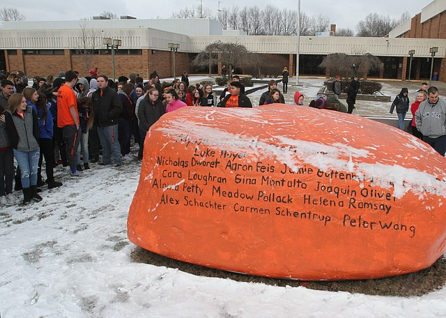 Students at Lordstown High School gather around a rock with names of Florida school shooting victims as part of national walk out day on March 14, 2018.  Photo by William D. Lewis - The Vindicator