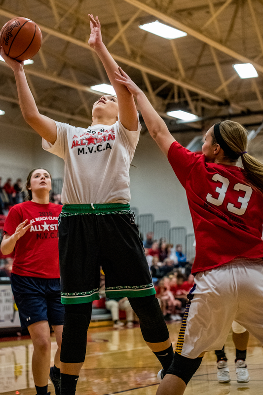 West Branch's Natalie Zuchowski shoots over the defense of Champion's Megan Turner as Brookfield's Tori Sheehan looks on during the Al Beach Classic held at Canfield High School on Tuesday.