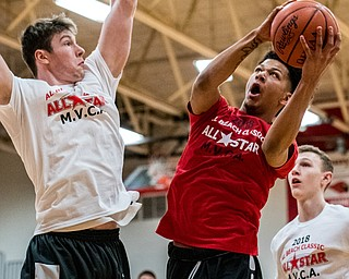 Warren G. Harding's Chris Hughes shoots over Struthers' Ryan Leonard as Boardman's Holden Lipke looks on during the Al Beach All-Star Classic on Tuesday at Canfield High School...?