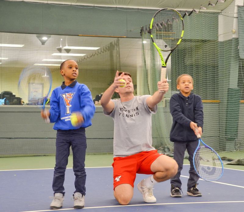 Pol Virgili Blanco, YSU sophomore international business major from Spain, coaches Ja'Viere Woods, left; first grade, and Sergio Shaw, right; kindergarten, both students from Youngstown Community School, on how to swing a tennis racket at the Boardman Tennis Center on March 23, 2018.    Photo by Scott Williams - The Vindicator