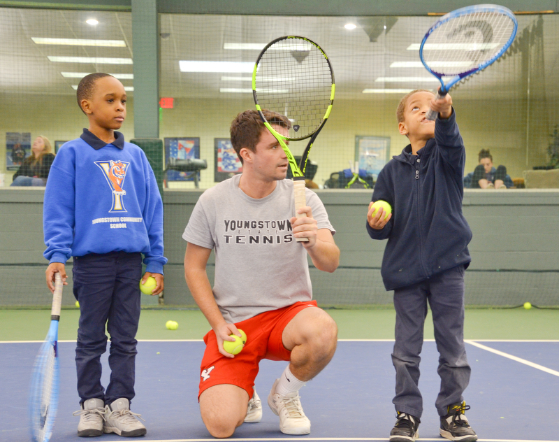 Pol Virgili Blanco, YSU sophomore international business major from Spain, coaches Ja'Viere Woods, left; first grade, and Sergio Shaw, right; kindergarten, both students from Youngstown Community School, on how to swing a tennis racket at the Boardman Tennis Center on March 23, 2018.    Photo by Scott Williams - The Vindicator .