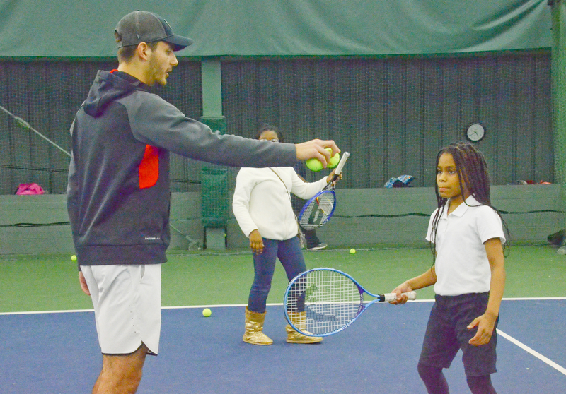 Vasileios Vardakis, YSU freshman business major from Greece, readies a ball for Mercedes Haskins, age 10; from Youngstown Community School, at the Boardman Tennis Center on March 23, 2018.  