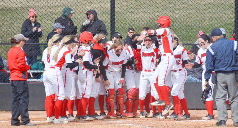 Lexi Zappitelli, #23, leaps in the air as she's about to be mobbed by her teammates after hitting one over the fence during game two against Indiana University-Purdue University Indianapolis March 24, 2018 at the Covelli Sports Complex at Youngstown State University.  Photo by Scott Williams - The Vindicator.