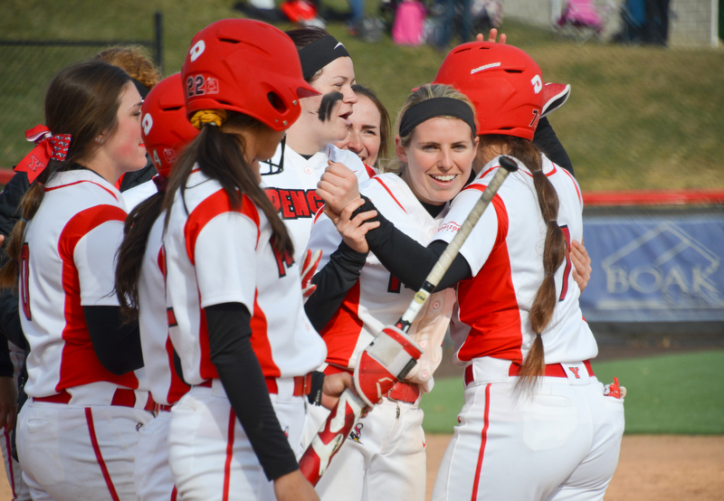 Kelly Thompson-Cappadocio, #7, gets a hug from Alexis Roach, #8, and smiles from her teammates after hitting enough runners in to call the game under mercy rule during game two against Indiana University-Purdue University Indianapolis March 24, 2018 at the Covelli Sports Complex at Youngstown State University.  Photo by Scott Williams - The Vindicator