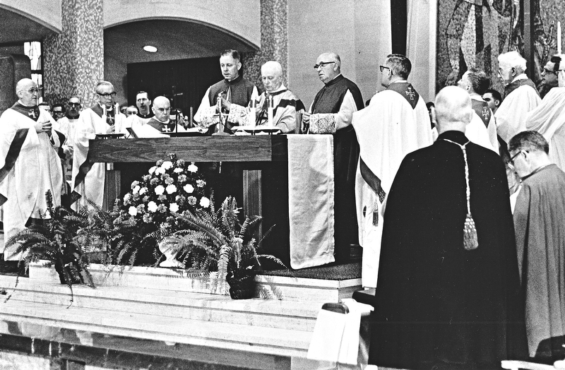Archbishop Alter, principal concelebrant of the funeral Mass is assisted by his chaplains, Msgr. Lettau (left) and Msgr. Gallagher (right).  Surrounding the main altar are Ohio bishops who concelebrated the Mass with the archbishop.  From the left they are: Bishop Clarence G. Issenman of Cleveland, Auxiliary Bishop E. A. McCarthy of Cincinnati, Auxiliary Bishop Clarence Elwell of Cleveland, the archbishop and chaplains, Bishop George A. Rehring, retired bishop of Toledo, Bishop John King Mussio of Steubenville, and the Most Rev. James W. Malone, apostolic administrator of the Diocese of Youngstown.