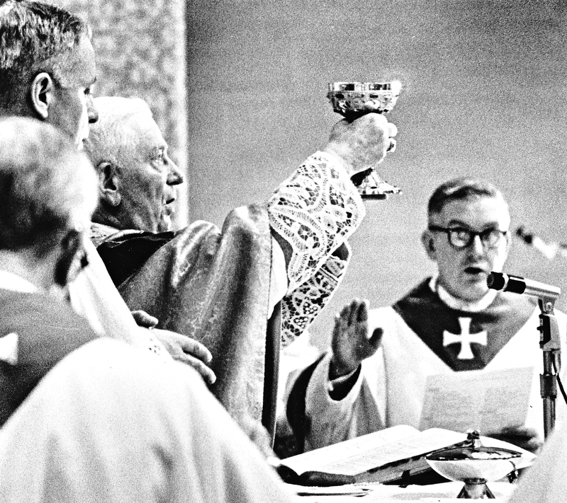 "The ""Chalice of Salvation"" is raised during the consecration of the funeral Mass by Archbishop Alter.  Bishop Malone is at right and Msgr. Lettau at left.