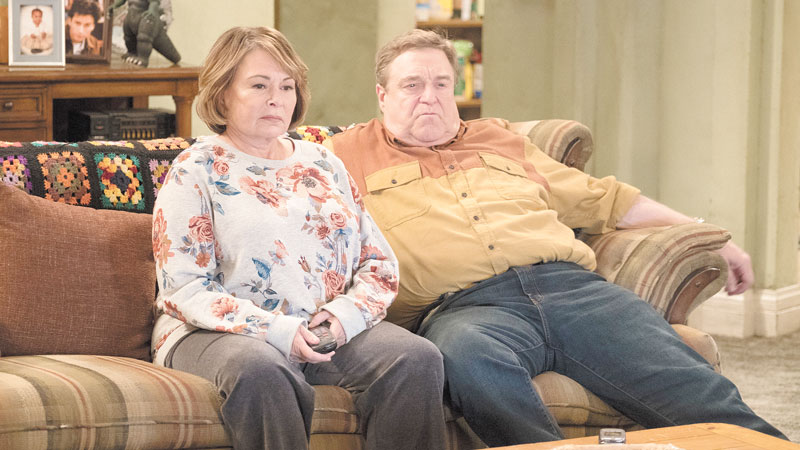 "Roseanne Barr looks more glamorous, John Goodman slimmer. But the mass-market plaid couch is a giveaway that ABC's ""Roseanne"" revival hasn't ditched its roots."
